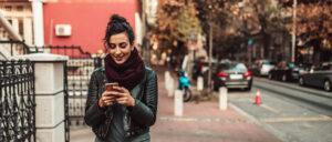 Mujer con smartphone cerca de una calle del centro de la ciudad