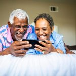 Couple watching show on smartphone 1024x683