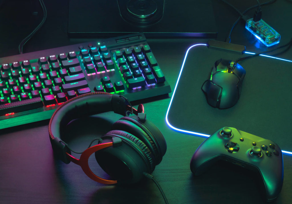 Gamer desktop setup with headphones mouse controller and RGB keyboard and mousepad