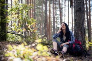 Excursionista femenina charlando por teléfono en el bosque