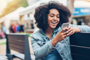 Mujer mirando celular fuera