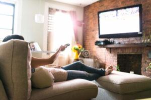 Mujer relajante en el sofá configurando su televisor inteligente