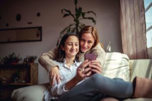 Mamá e hija usando un teléfono